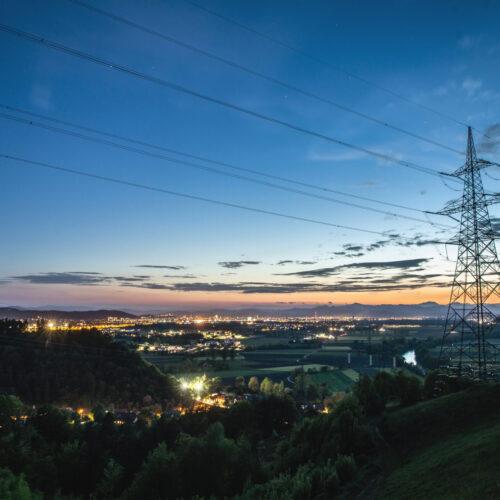 High,Power,Electricity,Pylon,Above,A,City,Skyline